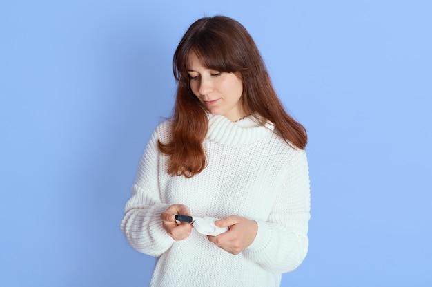 Zamyślona młoda kobieta ubrana w biały sweter z dzianiny dorywczo za pomocą kijów grzewczych tytoniu patrząc na to na niebiesko, pani z elektronicznym papierosem.