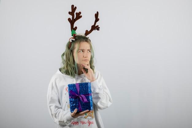 Zamyślona młoda kobieta w masce rogów jelenia trzyma prezent.