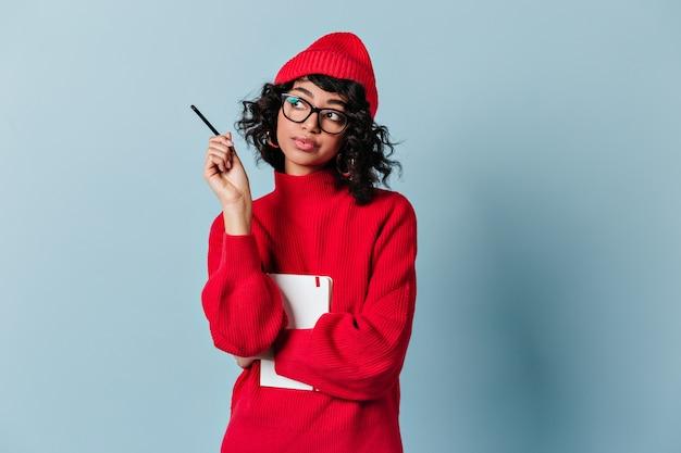 Zamyślona młoda kobieta w okularach i czerwonym kapeluszu, patrząc od hotelu