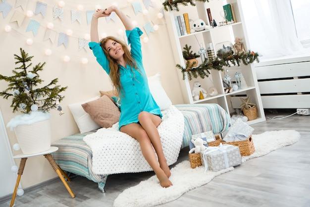 Zamyślona młoda kobieta z okazji bożego narodzenia. kobieta obudziła się w nowym roku. przytulne jasne wnętrze. dziewczyna w długiej niebieskiej koszuli