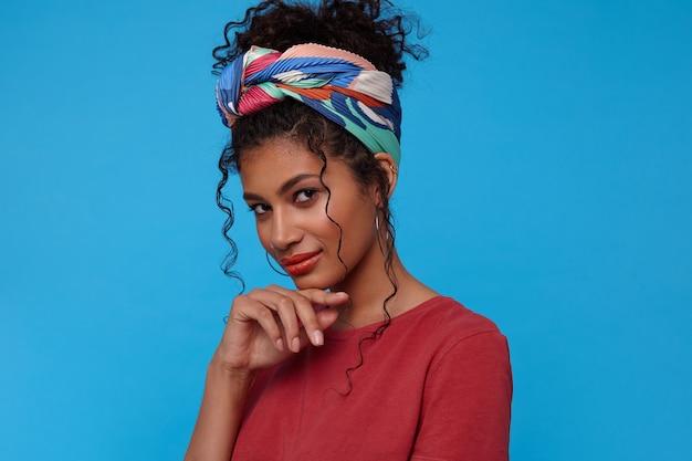 Zamyślona młoda, ładna brązowooka, kręcona kobieta z przypadkową fryzurą, opierająca brodę na uniesionej dłoni i uśmiechnięta lekko, patrząc delikatnie z przodu, pozująca nad niebieską ścianą