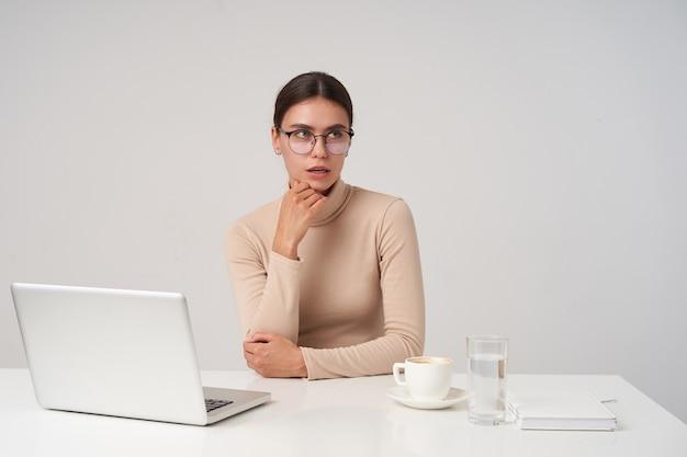 Zamyślona młoda ładna brunetka kobieta opierająca brodę na uniesionej dłoni i patrząc w zamyśleniu, w okularach i oficjalnym ubraniu, siedząc przy stole nad białą ścianą
