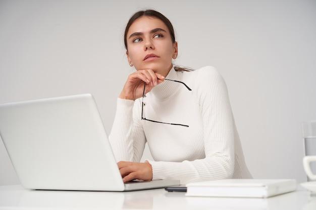 Zamyślona młoda ładna ciemnowłosa dama mrużąca oczy i trzymająca okulary, patrząc w zamyśleniu na bok, ubrana w formalne ubrania, siedząc na białej ścianie