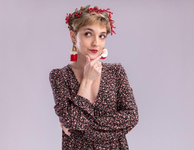 Zamyślona młoda ładna dziewczyna ubrana w świąteczny wieniec i blichtrową girlandę wokół szyi dotykającą podbródka patrzącą na bok z świątecznymi dekoracjami zwisającymi z jej uszu na białej ścianie z kopią miejsca