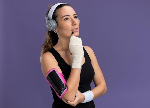 Zamyślona młoda ładna sportowa dziewczyna nosząca opaskę na głowę słuchawki i opaskę na telefon z uszkodzonym nadgarstkiem owiniętym bandażem patrząc w górę dotykając podbródka