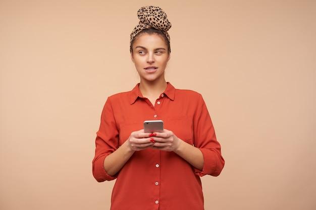 Zamyślona młoda piękna brunetka kobieta z pałąkiem na głowę trzymając smartfon w uniesionych rękach i patrząc w zamyśleniu na bok, odizolowana na beżowej ścianie
