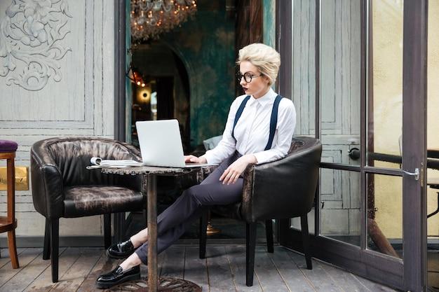 Zamyślona młoda piękna kobieta pracująca z laptopem na zewnątrz w kawiarni