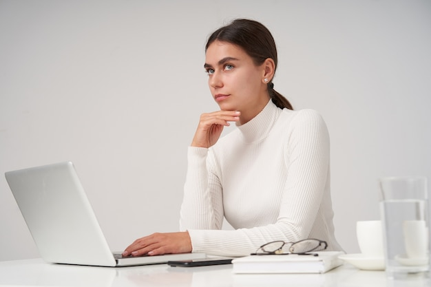 Zamyślona młoda śliczna ciemnowłosa kobieta z naturalnym makijażem trzymająca brodę z uniesioną ręką i patrząca w górę z założonymi ustami, pozująca na białej ścianie