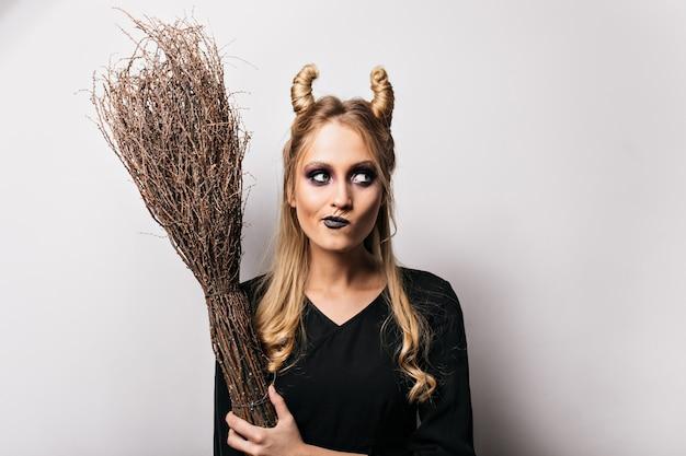 Zamyślona młoda wiedźma stojąca na białej ścianie podczas sesji halloweenowej. uroczy czarodziejka trzyma jej magiczną miotłę.