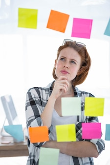 Zamyślona modniśka, stojąca w swoim biurze, czytająca notatki na wszystkim