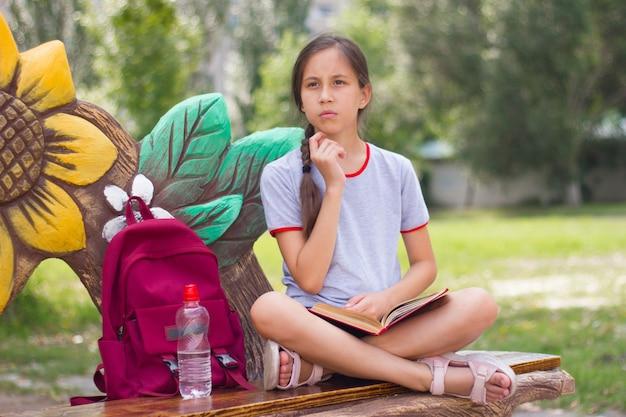 Zamyślona nastolatka siedzi w parku, trzymając książkę w rękach, patrząc na bok powrót do koncepcji szkoły