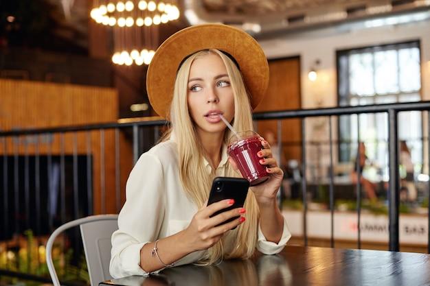 Zamyślona niebieskooka młoda blondynka modna kobieta w stylowych ubraniach siedzi nad nowoczesnym wnętrzem kawiarni i pije smoothie ze słomką, patrząc na bok w zamyśleniu z telefonem komórkowym w dłoni
