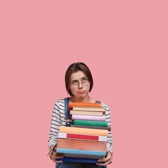 Zamyślona niezadowolona dama nosi stosy książek, nosi okulary optyczne