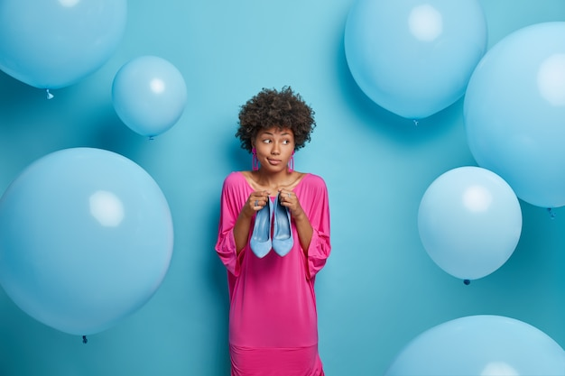 Zamyślona niezdecydowana kobieta myśli, co nosić na nogach, aby dopasować sukienkę, trzyma niebieskie buty na obcasie, sukienki na przyjęcie urodzinowe, nosi fantazyjną długą różową sukienkę, odizolowana na ścianie, balony powietrzne