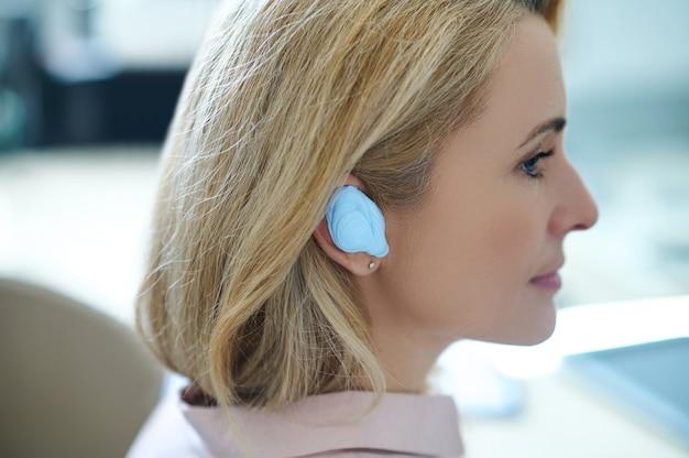 Zamyślona pacjentka z silikonową wkładką uszną wpatrująca się w dal