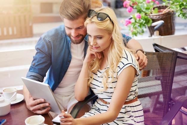 Zamyślona para za pomocą cyfrowego tabletu w kawiarni