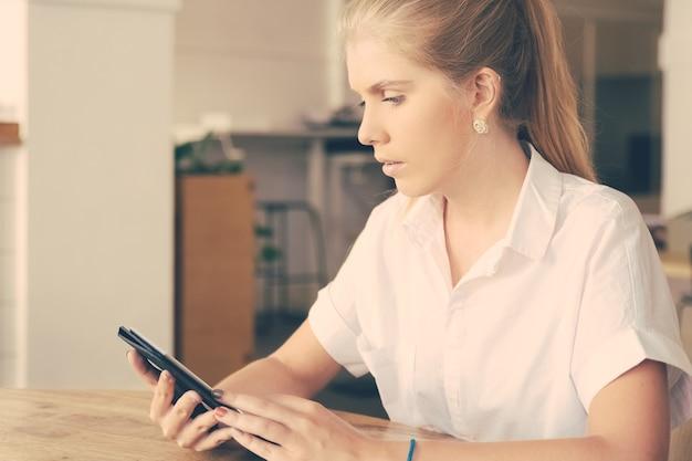 Zamyślona piękna blondynka ubrana w białą koszulę, siedząca przy stole w przestrzeni coworkingowej za pomocą tabletu