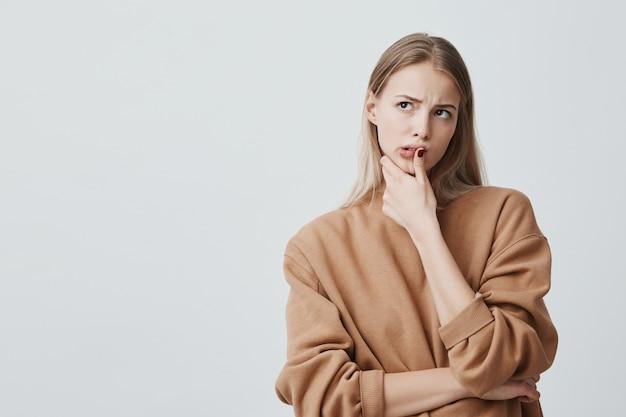 Zamyślona piękna kobieta o długich blond włosach, spoglądająca w górę z zamyślonymi minami, coś planuje, stawia przed pustą ścianą. poważna skoncentrowana kobieta trzyma palec na brodzie
