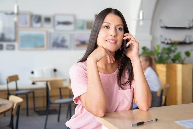 Zamyślona piękna młoda kobieta rozmawia przez komórkę, stojąc w coworkingu, opierając się na biurku, odwracając wzrok i uśmiechając się