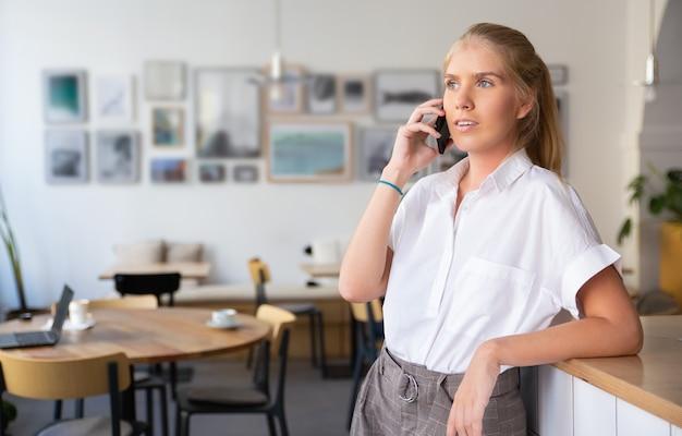 Zamyślona piękna młoda kobieta ubrana w białą koszulę, rozmawiając przez telefon komórkowy, stojąc w przestrzeni coworkingowej i odwracając wzrok