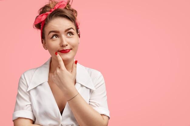 Zamyślona pinup śliczna kobieta wygląda z rozmarzonym wyrazem w górę, myśli o czymś, wyobraża sobie miłe chwile z bliską osobą