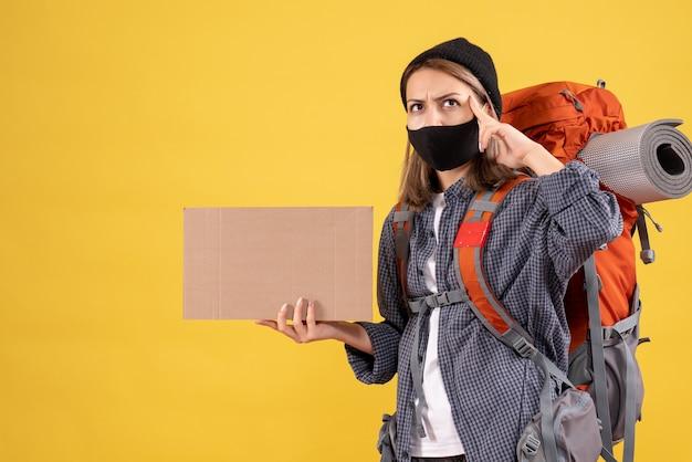 Zamyślona podróżniczka z czarną maską i plecakiem trzymająca karton