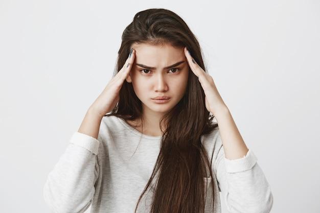 Zamyślona poważna, skoncentrowana brunetka modelka trzyma palce na skroniach, próbuje zapamiętać ważne informacje