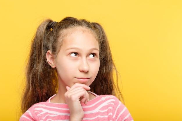 Zamyślona, przemyślana dziewczyna, patrząc w górę i na boki. portret na żółto.