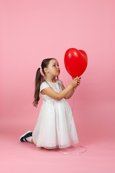 Zamyślona rozmarzona dziewczyna w białej sukni klęczy i patrzy na czerwony balonik w kształcie serca