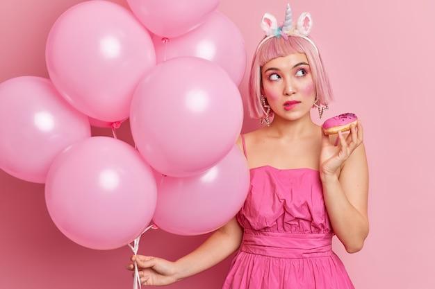 Zamyślona różowowłosa kobieta przygryza wargi i patrzy w bok, myśli o czymś, co trzyma glazurowane pączki