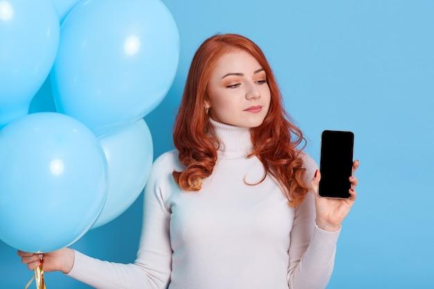 Zamyślona rudowłosa europejka myśli, że obchodzi przyjęcie urodzinowe, trzyma w dłoniach nowoczesny telefon komórkowy z pustym ekranem i bukietem balonów z helem, nosi biały golf, kobieta odwraca wzrok.