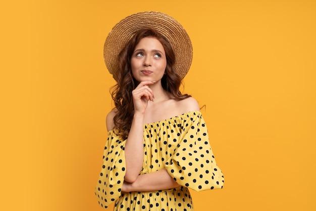 Zamyślona rudowłosa kobieta pozuje w żółtej sukience z rękawami na żółto. letni nastrój.