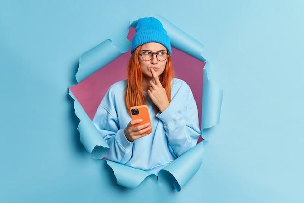 Zamyślona rudowłosa kobieta trzyma telefon komórkowy z zamyślonym wyrazem twarzy trzyma palec wskazujący w pobliżu warg przegląda w internecie nad odebraną wiadomością nosi kapelusz, a sweter przebija się przez niebieską papierową ścianę