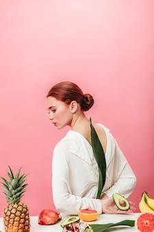 Zamyślona rudowłosa kobieta z ananasem, bananami, granatami i kiwi. studio strzał atrakcyjnej dziewczyny z tropikalnymi owocami na różowym tle.