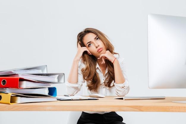 Zamyślona śliczna młoda bizneswoman siedzi i używa telefonu komórkowego w miejscu pracy na białym tle