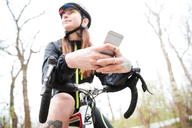 Zamyślona śliczna młoda kobieta na rowerze przy użyciu telefonu komórkowego w parku