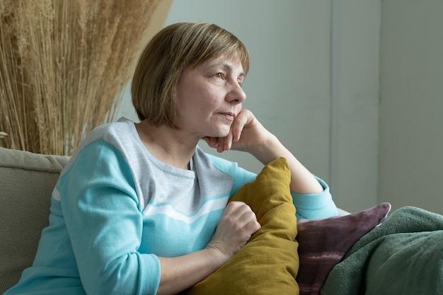 Zamyślona starsza kobieta siedzi na sofie i wygląda przez okno