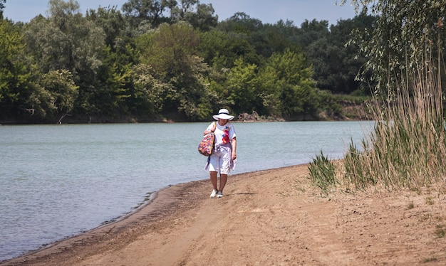 Zamyślona staruszka, emerytka w podeszłym wieku, wypoczynek na piasku nad rzeką, pojęcie czasu i wieku, wakacje na świeżym powietrzu, zdrowy tryb życia