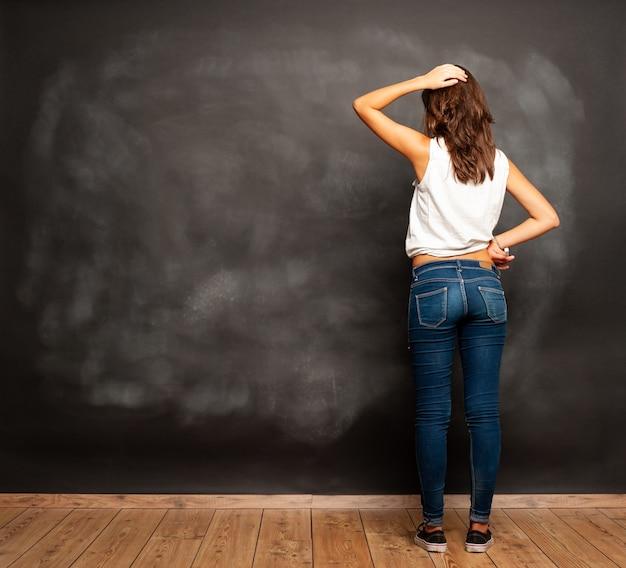 Zamyślona studentka stojąca przed pustą tablicą