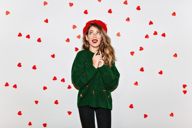 Zamyślona stylowa kobieta w modnym berecie, odwracając wzrok na ścianie serca