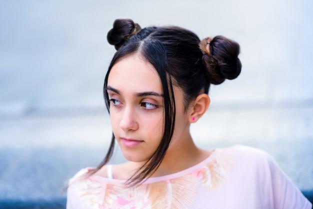 Zamyślona stylowa nastoletnia brunetka z kokami odwracająca wzrok marzycielsko na rozmytym tle