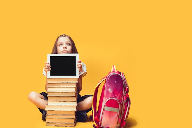 Zamyślona uczennica wygląda zza stosu książek i koncepcji edukacji dla dzieci na tablecie