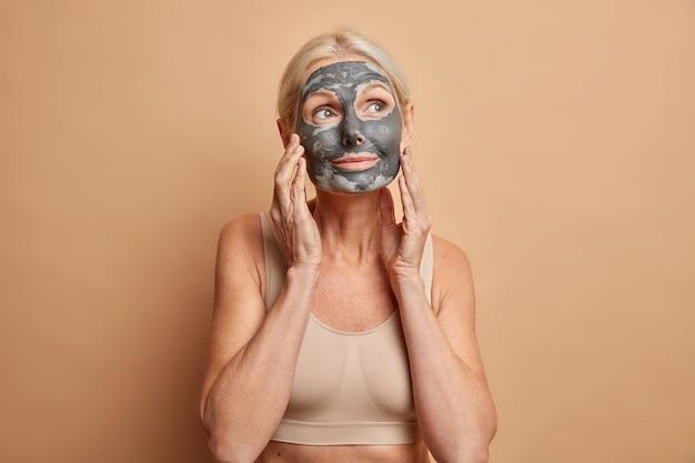 Zamyślona, urocza dama w średnim wieku ma minimalny makijaż, nosi maskę nawilżającą, delikatnie dotyka twarzy ubranej w luźne topy na beżowej ścianie