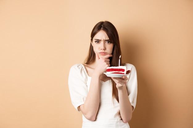 Zamyślona urodzinowa dziewczyna marszcząca brwi i myśląca o życzeniu trzymająca tort ze świecą stojącą na beżowej ba...