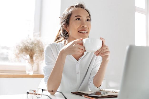 Zamyślona uśmiechnięta azjatycka biznesowa kobieta pije kawę i odwraca wzrok, siedząc przy stole w biurze