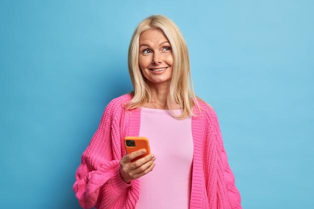 Zamyślona, zadowolona, wesoła blondynka o przyjemnym wyglądzie używa telefonu komórkowego do komunikacji online ubrana w ciepły, różowy sweter z dzianiny.