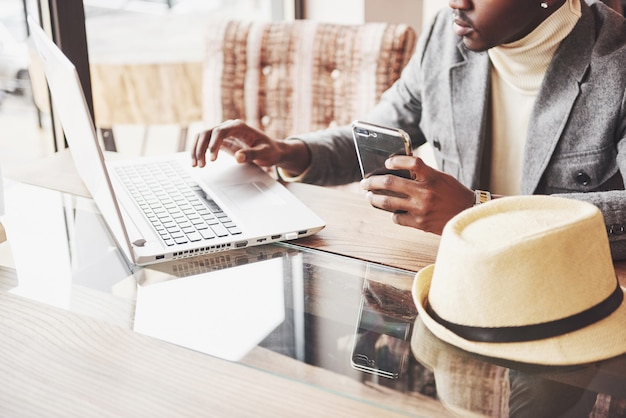 Zamyślony afro amerykański przystojny profesjonalny pisarz popularnych artykułów na blogu, ubrany w modny strój i okulary zastanawiając się nad nową historią, korygując swój scenariusz z notatnika siedzącego w kawiarni