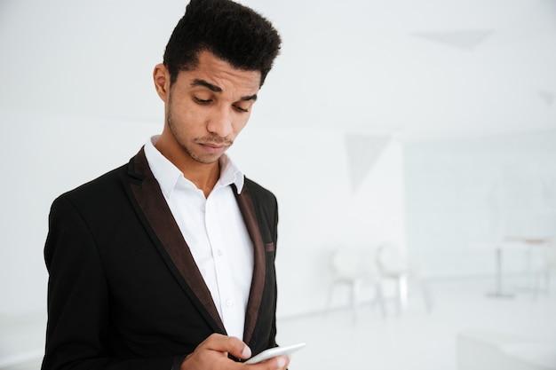 Zamyślony afrykański biznesowy mężczyzna w czarnym garniturze piszący wiadomość na telefonie w biurze