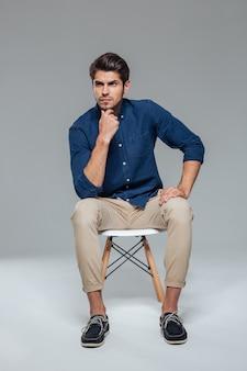Zamyślony, atrakcyjny, dorywczo młody człowiek siedzący na krześle nad szarą ścianą