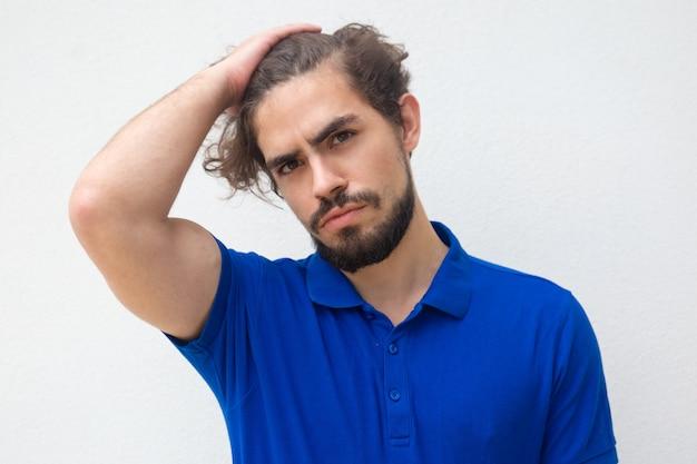 Zamyślony atrakcyjny facet dotyka głowy